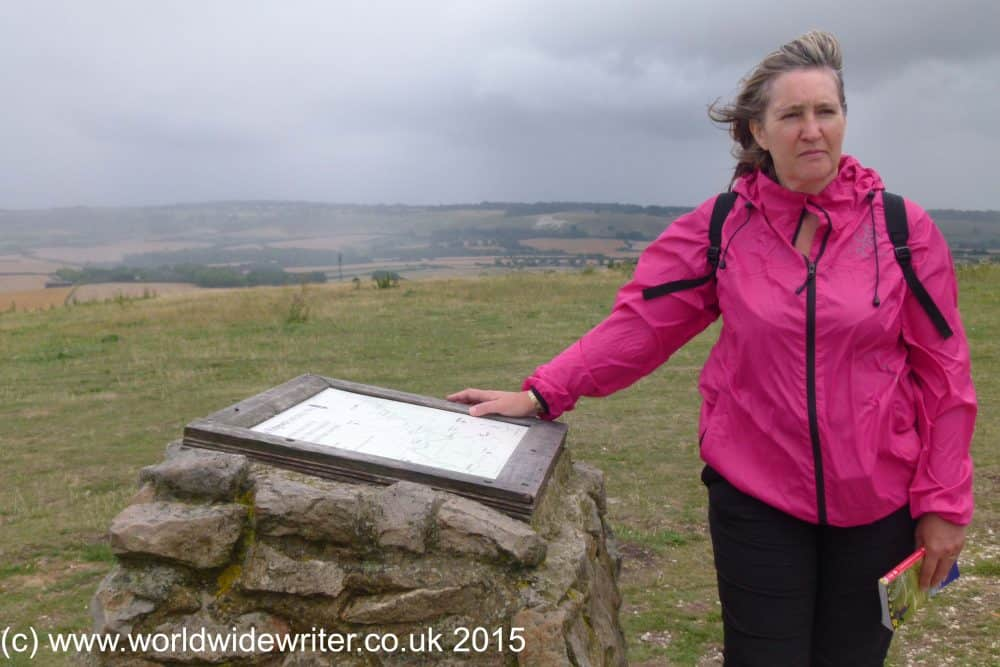 Walker standing by marker stone at the end of the Ridgeway path