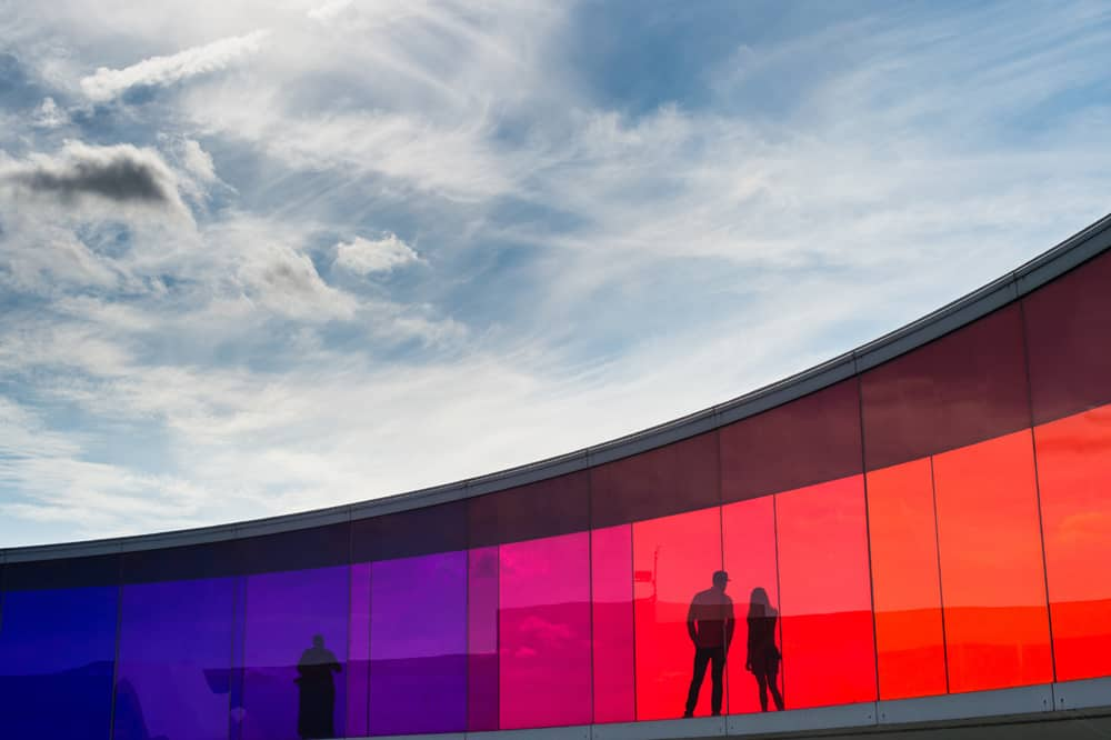 Two figures inside a walkway covered with red and purple glass