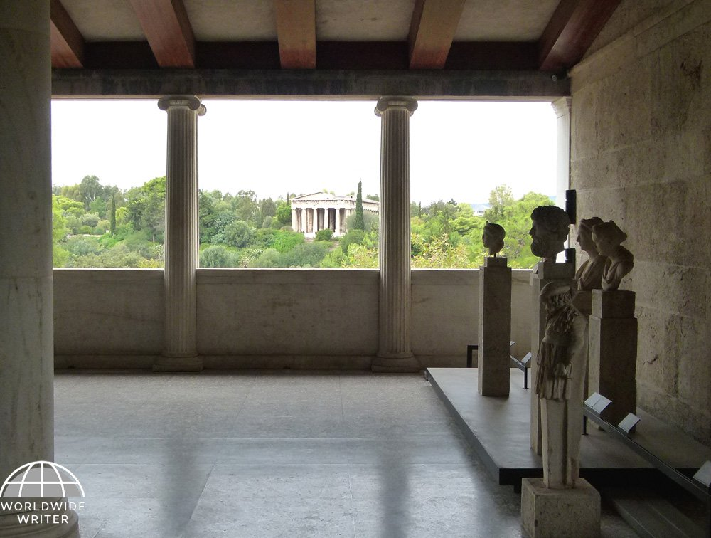 Interior of museum with statues, and window looking out on trees and a temple