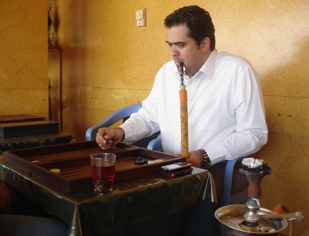 Man with a pipe and a drink playing backgammon