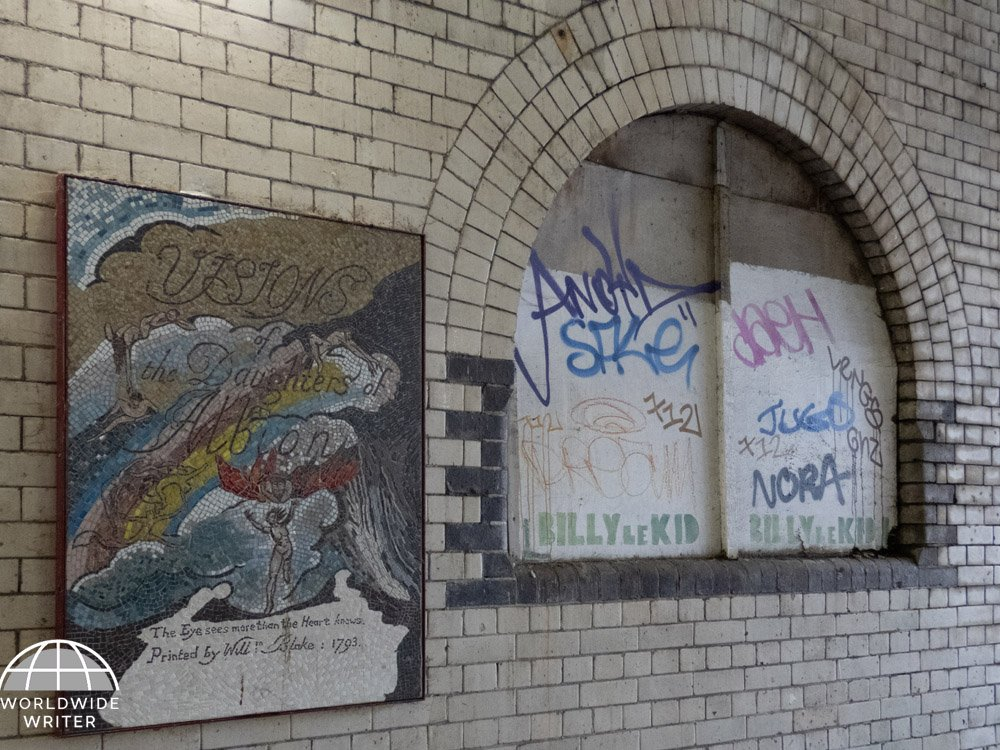 Brick wall with mosaic picture next to a blocked-up window covered with graffiti