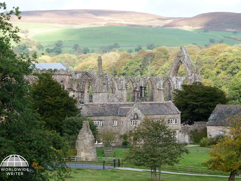Abbey ruins surrounded by trees and with the hills of the Yorkshire Dales behind