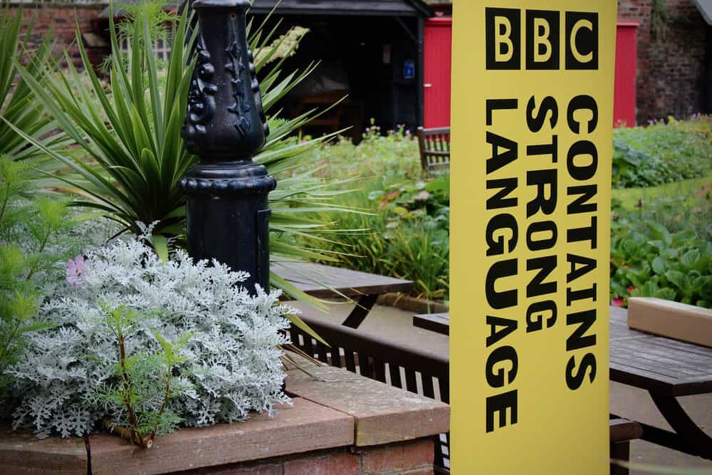 "Garden with yellow signboard saying ""Contains strong language"", one of the events for UK City of Culture 2021"