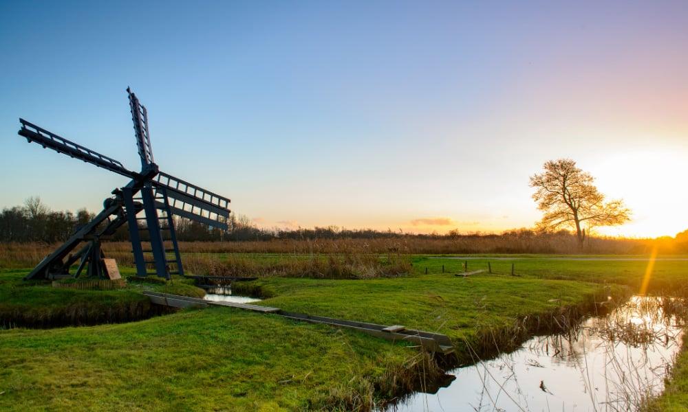 Windmill and canal in the Weerribben-Wieden National Park, one of the hidden gems of Steenwijk