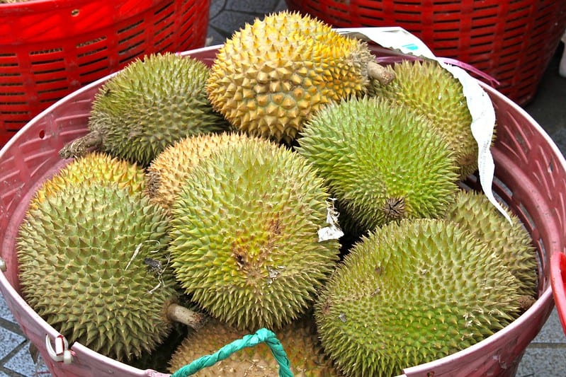 Whole durian are green and covered with spikes