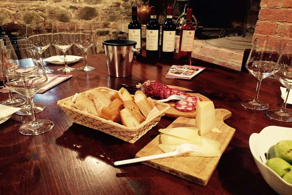 Bread, meat and cheese with wine bottles