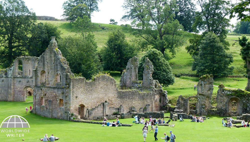 People on the grass in front of a ruined abbey with a backdrop of hills and trees