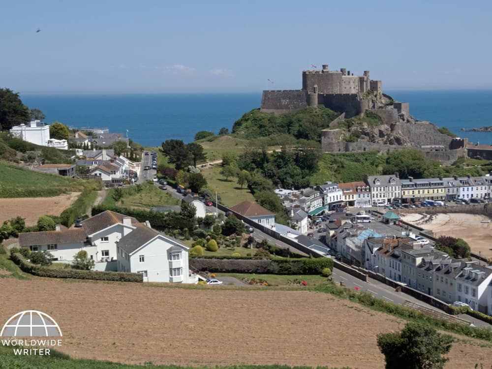 Castle on a hill top and village beneath it with white houses, beach and the sea