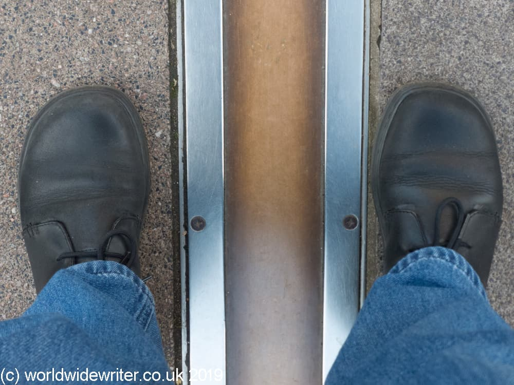 One foot on either side of the Meridian Line