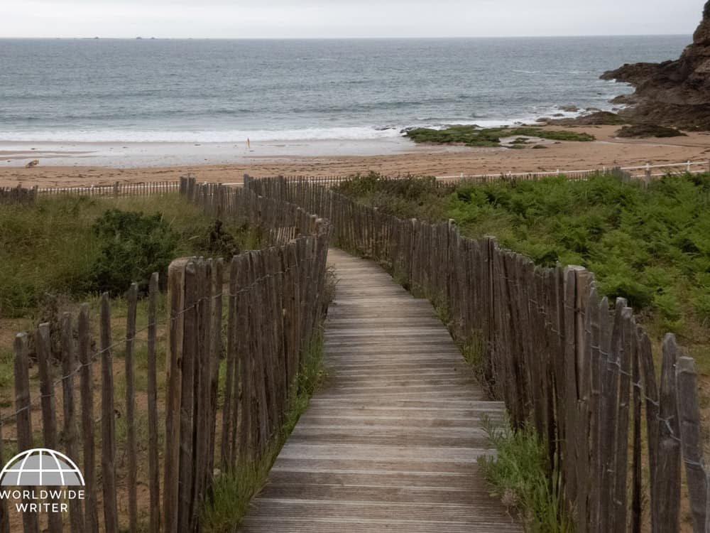 Wooden steps edged with fence and grassy area leading to the beach and the sea