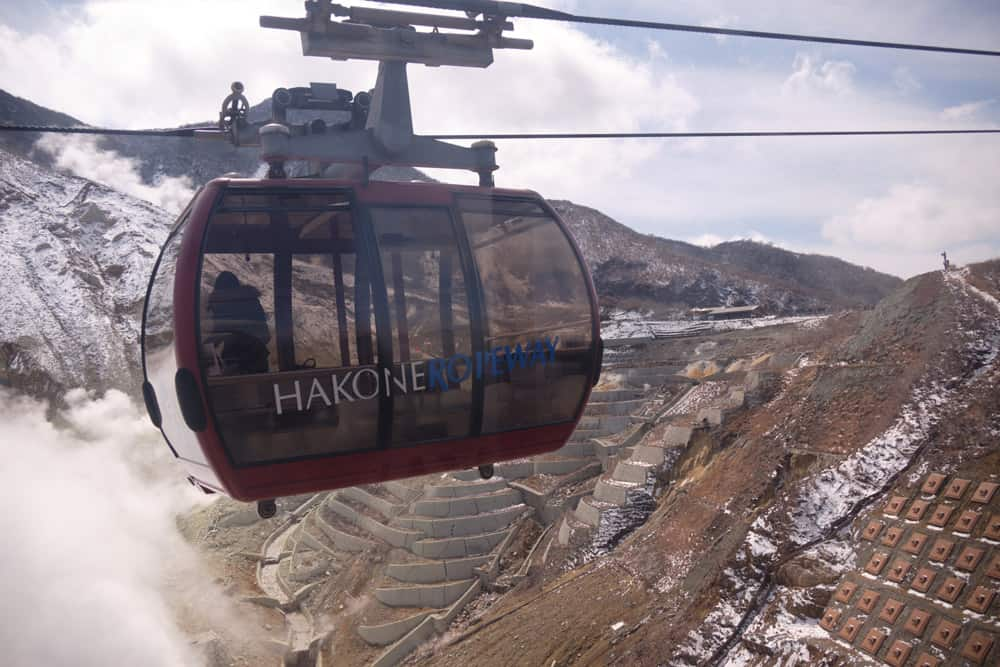 Cable car travelling over mountains with terraces and steam vents, one of many things to do in Hakone