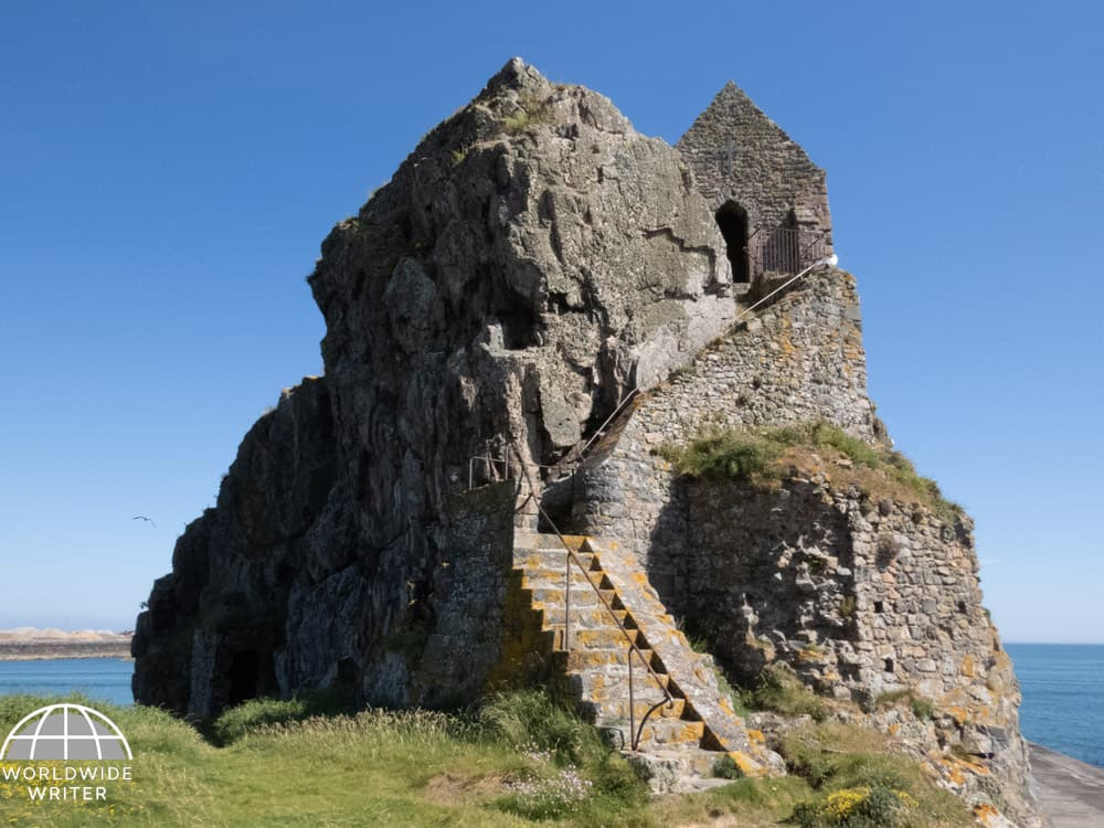 Stairway on the side of a big rock leading to an ancient chapel at the top