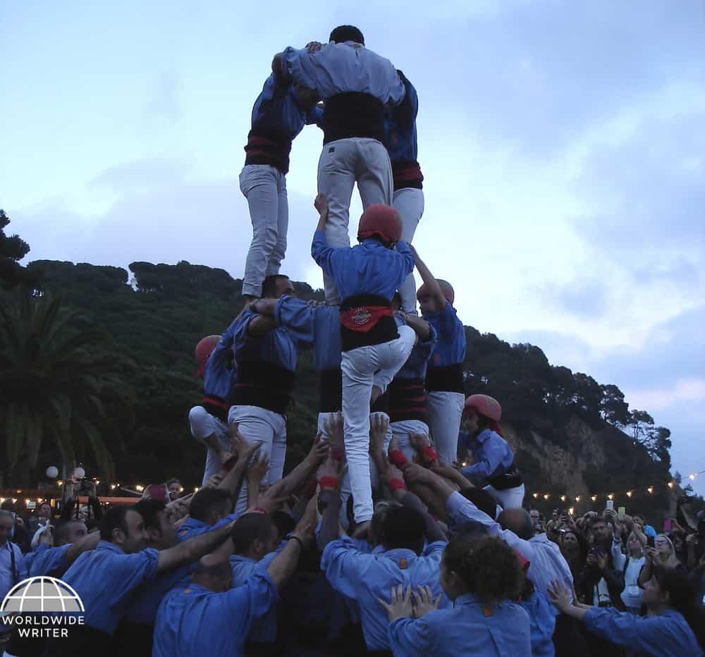 Men climbing onto the top of a human pyramid