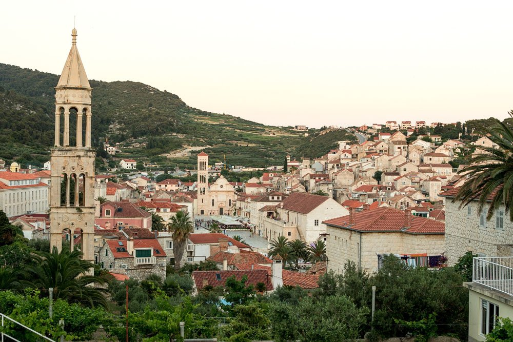 Town with red roofed houses and a tall tower and a backdrop of mountains