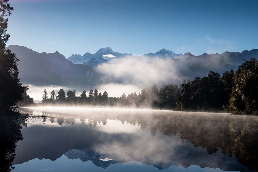 Misty morning with mountains and trees reflected in a lake