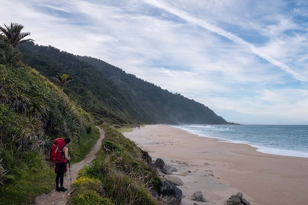 Hiker on a path with hills on one side and beach and sea on the other
