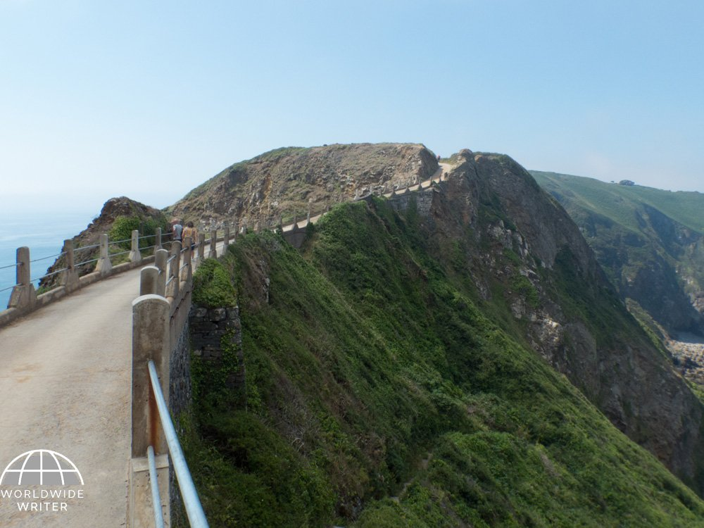 Narrow road between two islands with long steep drop down to the sea