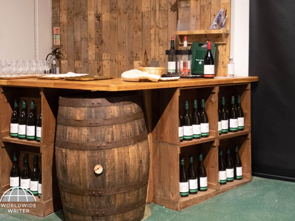 Wooden racks with bottles of wine beside a large barrel
