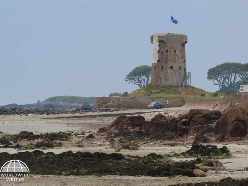Round tower with a flag at the top and rocky beach in front of it