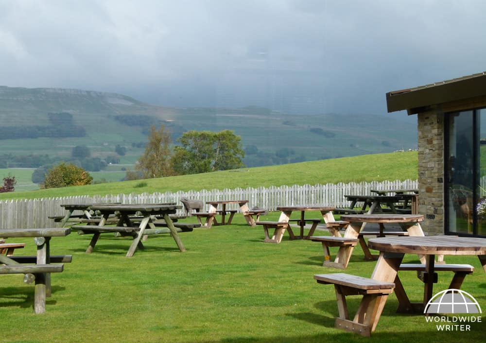 Outdoor restaurant tables at the Wensleydale Creamery, looking towards the hills of the Yorkshire Dales