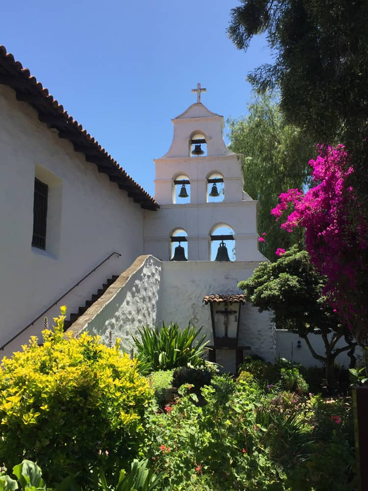 Part of the Mission, with bells in the wall, steps and trees and plants in front
