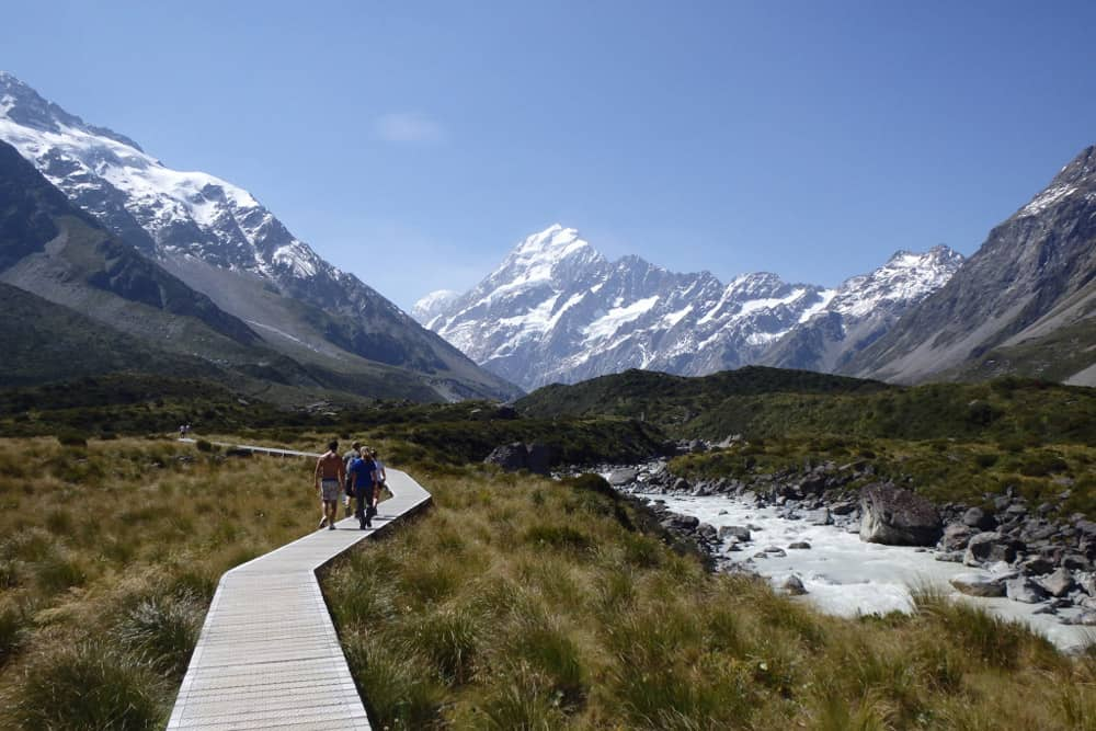 Tall mountains with ice and people hiking along a boardwalk