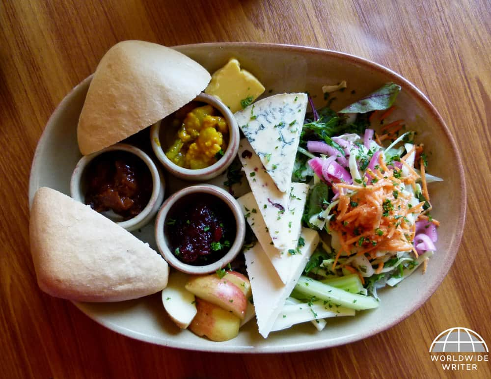 Plate of cheese with bread, pickles and salad