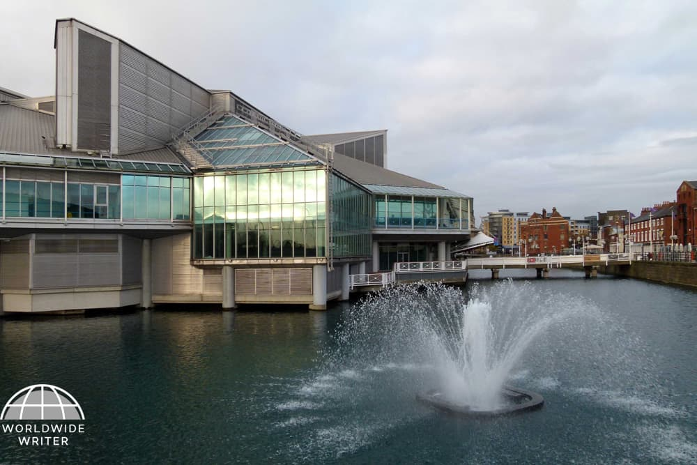 Modern shopping centre surrounded by water with a fountain