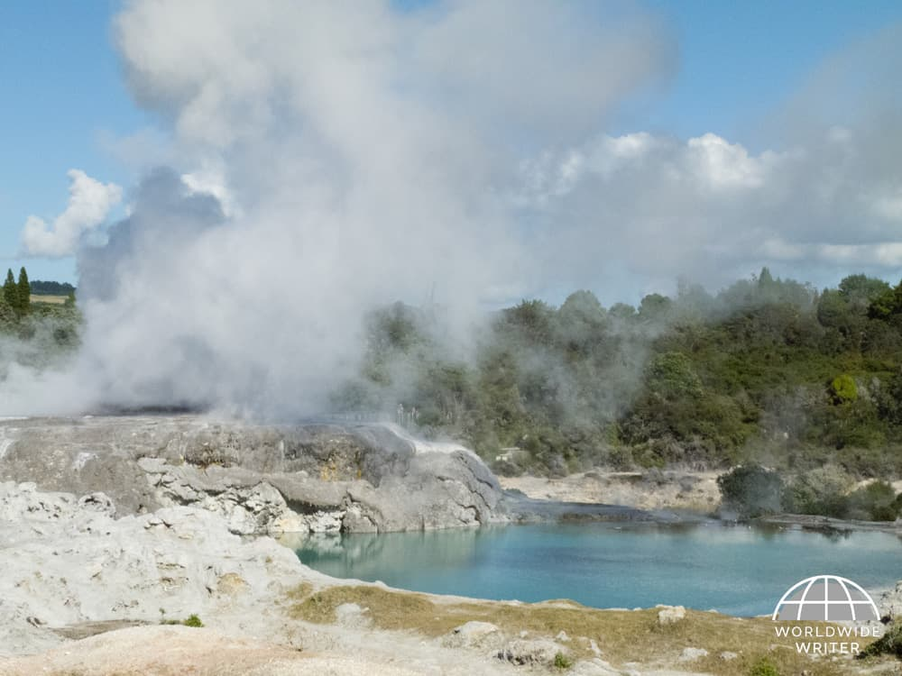 Thermal landscape with water and steam escaping from a geyser