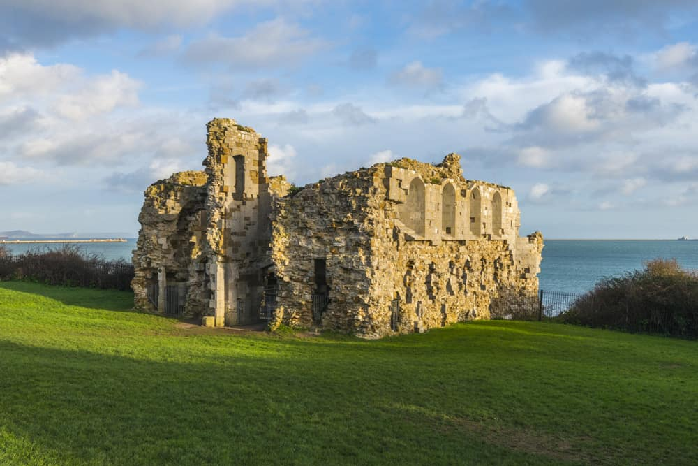Ruins of a castle with grass in front and sea and sky behind