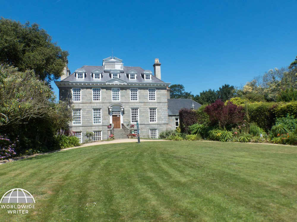 Large manor house with lawns and trees in front