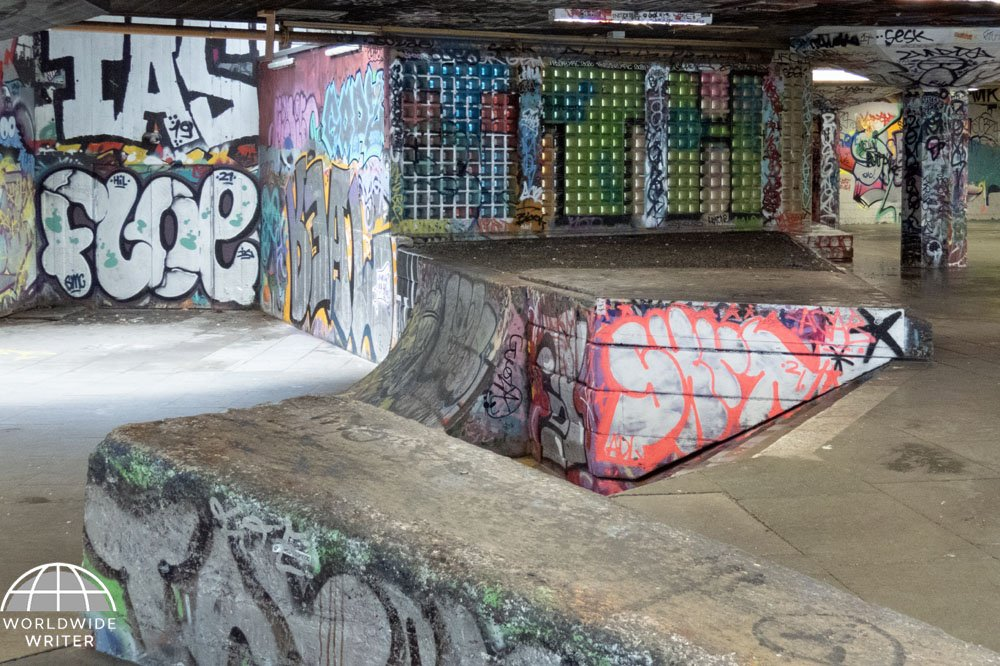 Skate park with ramps and pillars covered with drawings and graffiti