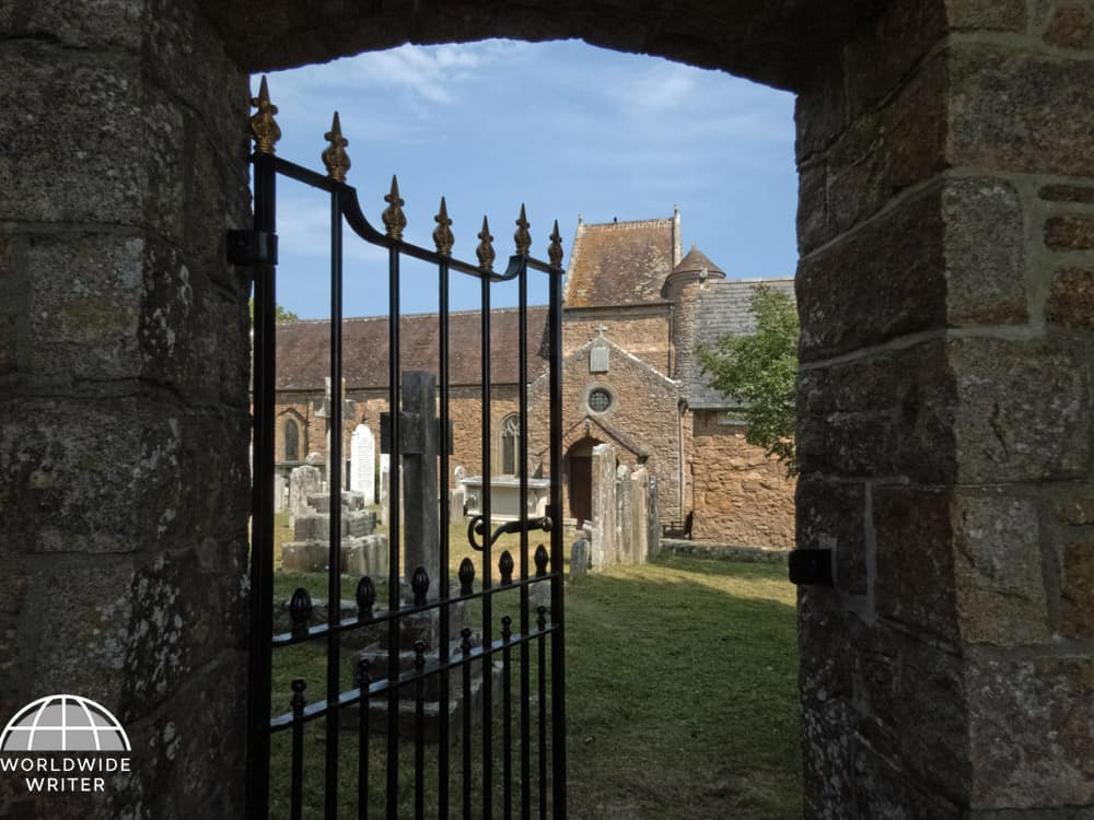 Gateway with open gate leading to grassy churchyard and church in the background