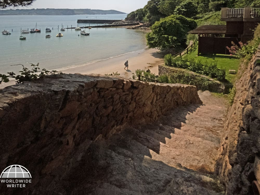 Stone steps leading downwards to the beach with trees and the sea in the background