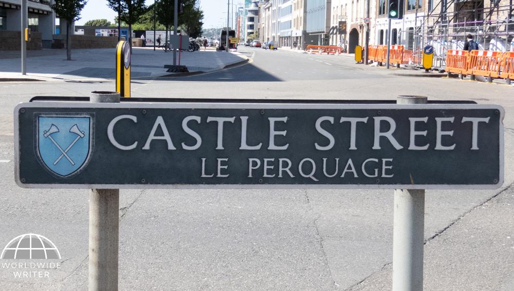 "Road sign saying ""Castle Street Le Perquage"""