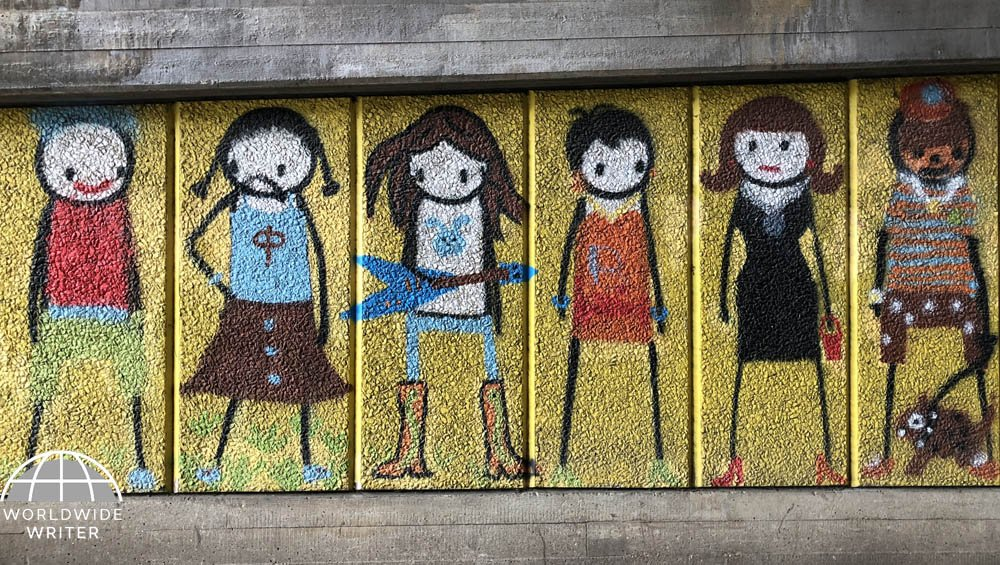 Six stick figures with brightly coloured clothes against a yellow background