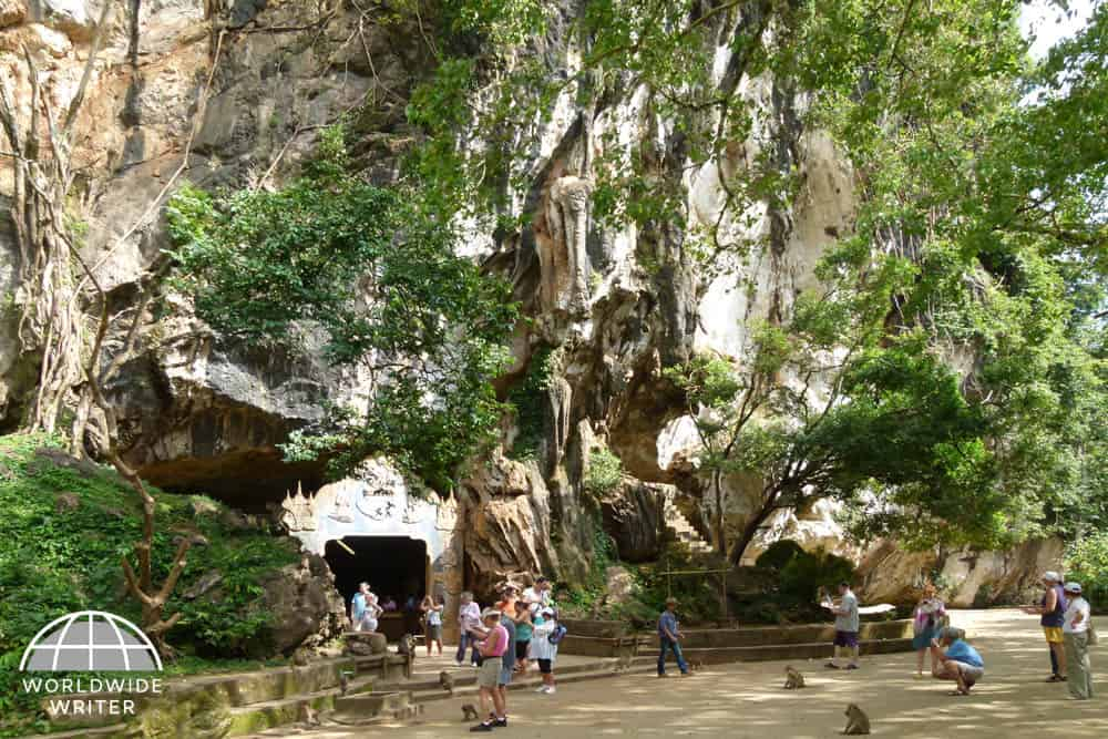 Exterior of cave temple, with tourists and monkeys