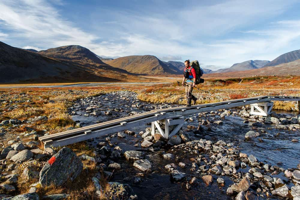 Hiker crossing a bridge in a remote landscape with rocks and mountains