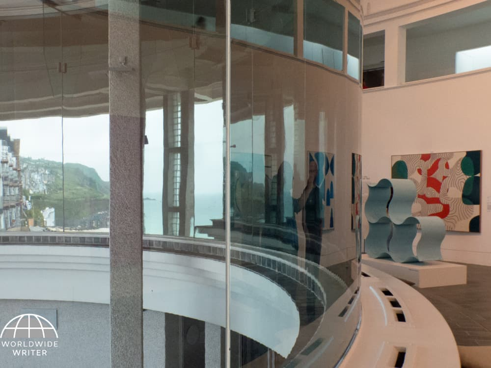 Curved gallery of the Tate St Ives, showing artworks and the town and sea glimpsed through the window