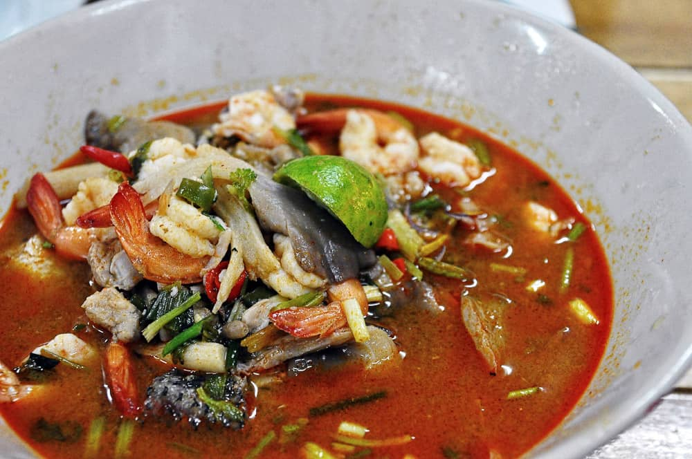 Bowl of red soup with prawns and vegetables