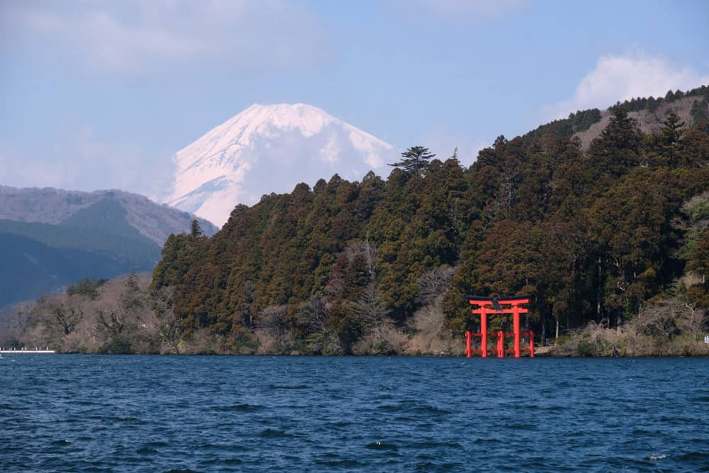 Lake with trees and Mount Fuji in the background and red torii gate by the side of the water