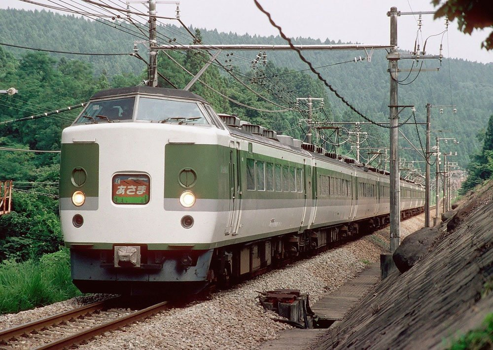 White train with overhead wires travelling through forest landscape - correct train etiquette is one of the things to know before visiting Japan
