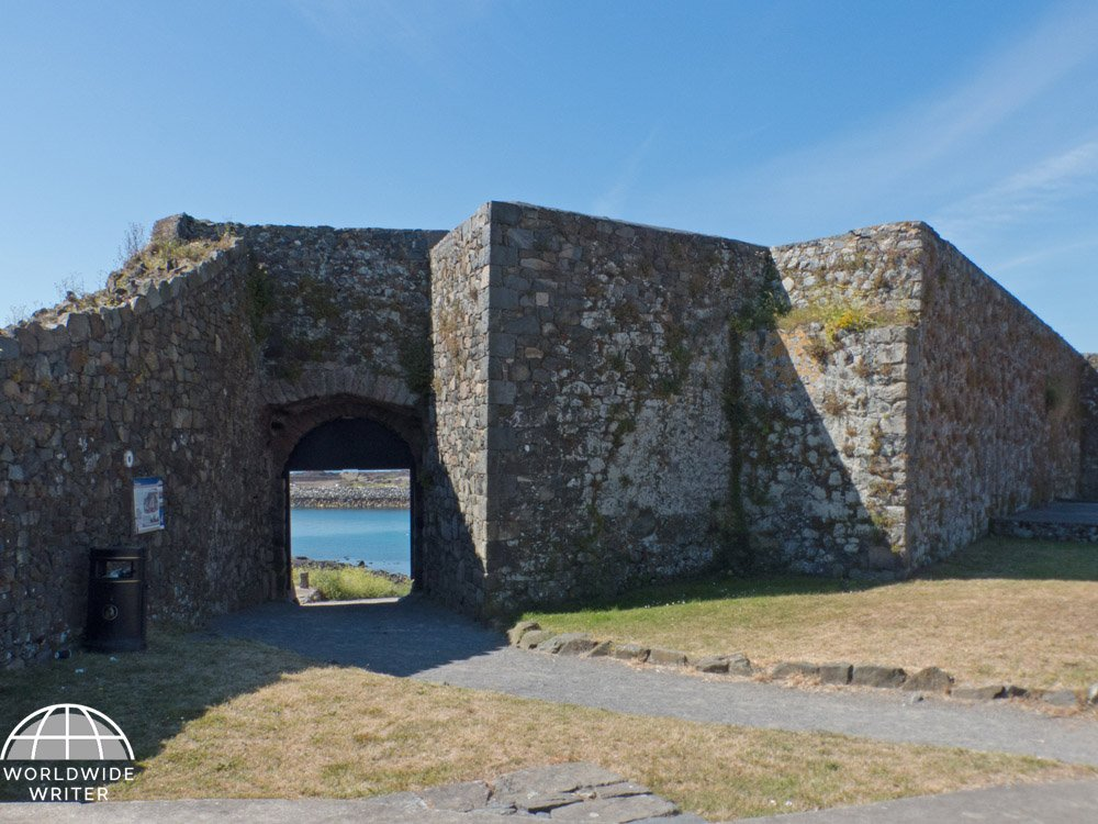 Remains of a grey stone castle with a view of the sea through a gateway