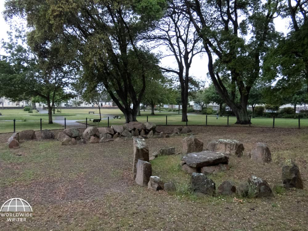 Stone circle and remains of a grave within a clearing surrounded by trees