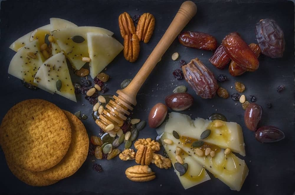 Board with cheese, dates and honey