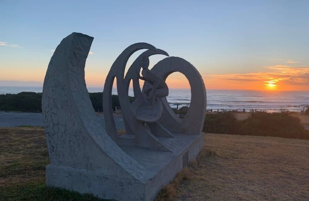 Beach with a sculpture of a surfer and waves